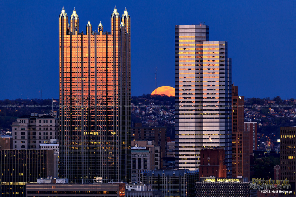 An orange full moon rises between PPG Place and One Oxford Center