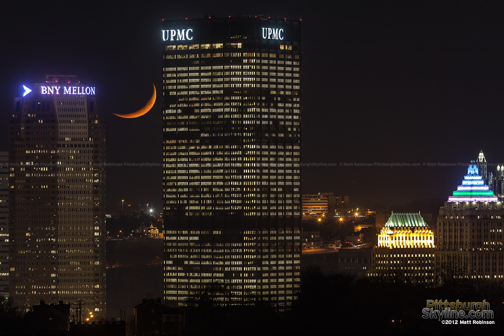 Crescent moon sets between the US Steel Tower and BNY Mellon Center on Light Up Night