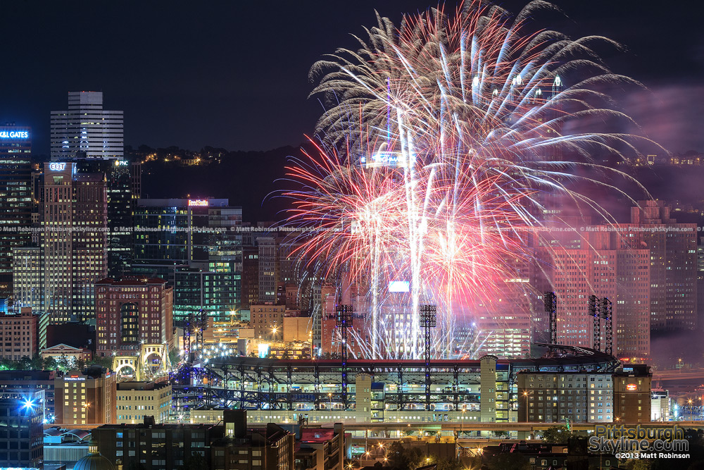 Fireworks explode between PNC Park and Pittsburgh skyscrapers