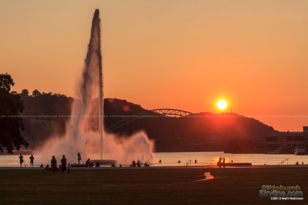 The sun sets over the Ohio River with the fountain at the Point
