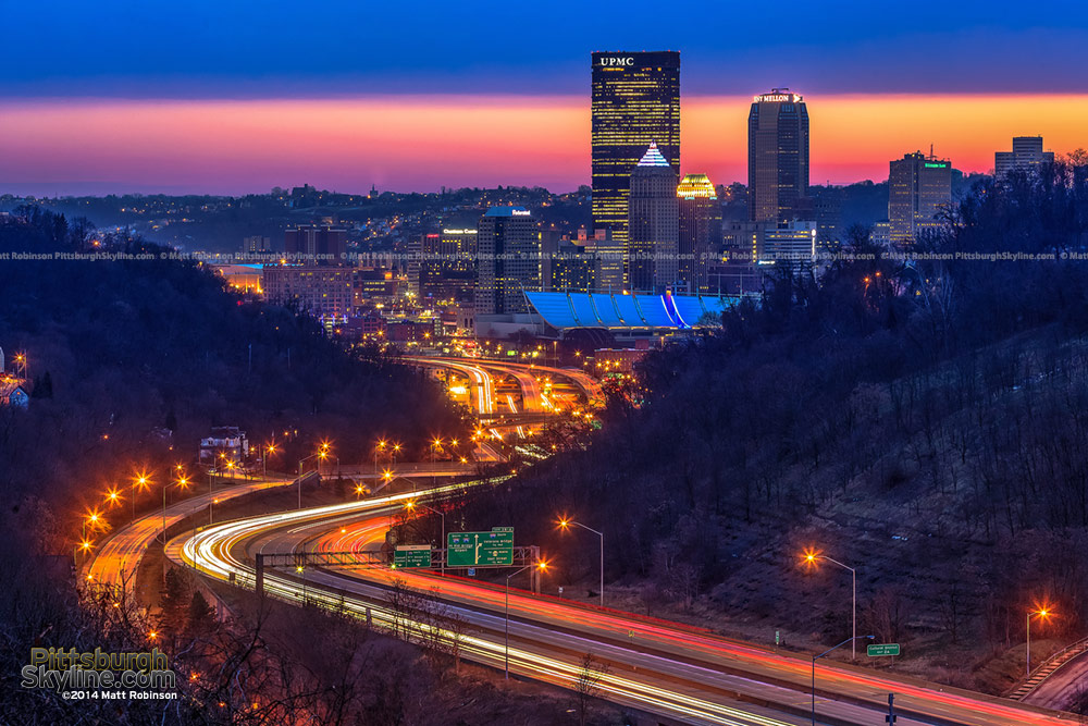 Interstate 279 streams into downtown Pittsburgh at sunset from City View